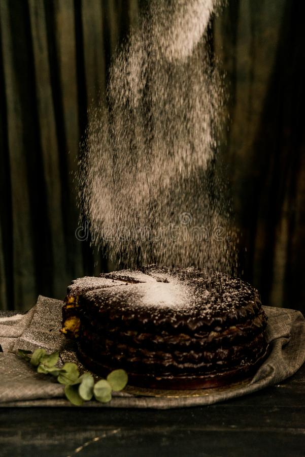 Covering chocolate cake with sugar powder. Close up decorating chocolate cake with sugar powder. Dark vintage stillife stock photography
