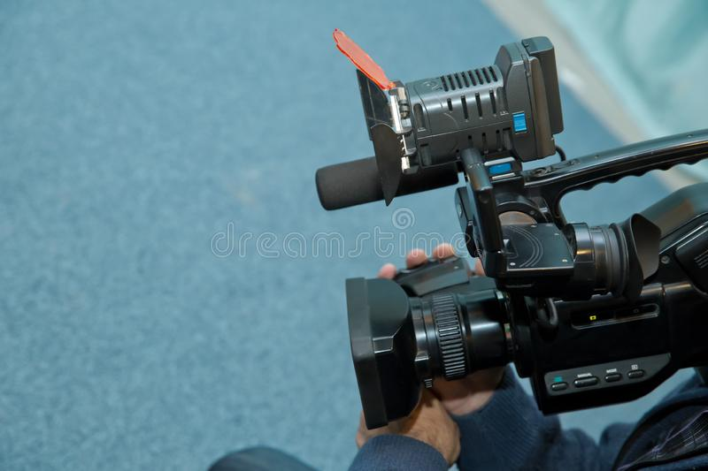 Covering an event with a video camera., Videographer takes video camera with free copy space for text., Video camera operator stock photos