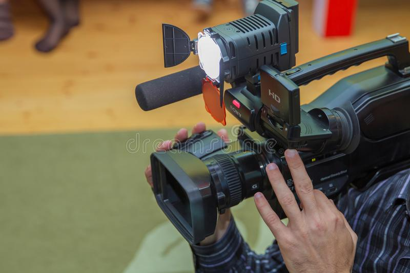 Covering an event with a video camera., Videographer takes video camera with free copy space for text., Video camera operator royalty free stock photo