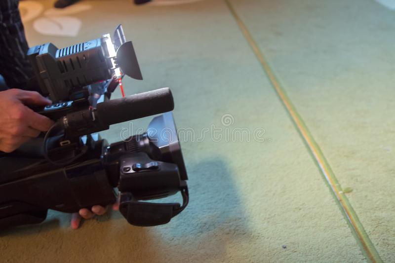 Covering an event with a video camera., Videographer takes video camera with free copy space for text., Video camera operator royalty free stock photography