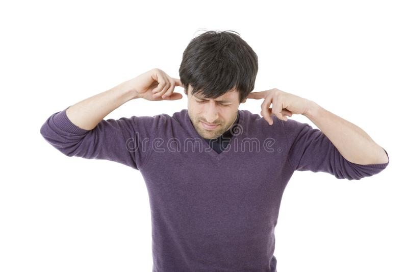 Covering his ears. Handsome young man covering his ears, isolated white background royalty free stock image
