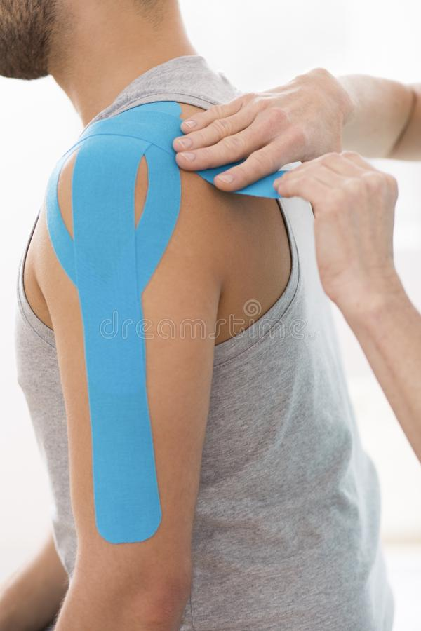 Physiotherapist covering selected fragments of young man`s body with special structure patches during kinesiotaping therapy. Covering selected fragments of young stock photos