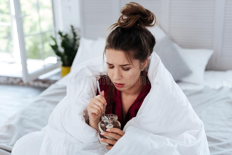 Woman covering in coverlet eating chocolate. In coverlet. Dark-haired woman covering in white coverlet eating chocolate and vanilla spread after stress at work royalty free stock image