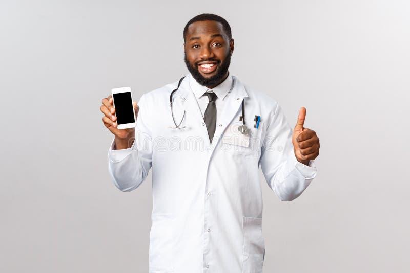 Covid19、流行病和在线任命概念 帅气微笑的非洲裔美国医生推荐使用移动应用 免版税库存照片