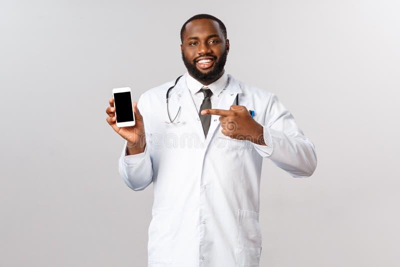 Covid19、流行病和在线任命概念 帅气的职业医生,非裔美国男医生指指点 库存照片
