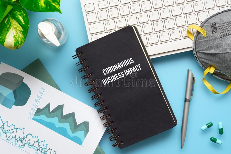 COVID-19 or Corona virus Business IMPACT background concept. Mockup Notebook for Covid 19 business impact anlysis with busines. Graphs sheets, N95 facial masks royalty free stock image