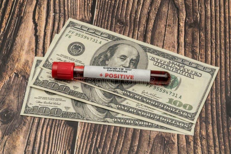 COVID 19 Coronavírus, amostra de sangue infectada no tubo de amostra, em dólares americanos, negócios com medicamentos fotos de stock