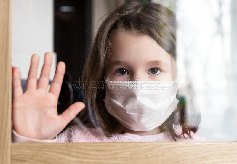 COVID-19 coronavirus concept, little girl in face mask looking through window at home or clinic. Portrait of sad kid during stock photo
