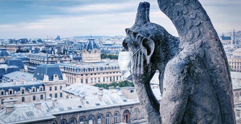 COVID-19 coronavirus in France, medical mask on gargoyle of Notre Dame in Paris. Tourist landmarks closed due to corona virus stock photography