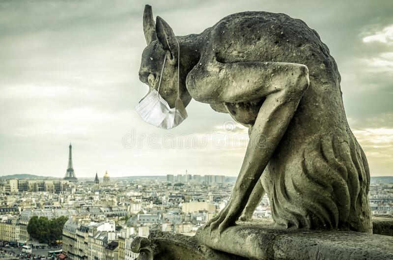 COVID-19 coronavirus in France, medical mask on gargoyle of Notre Dame in Paris. Tourist landmarks closed due to corona virus stock photos