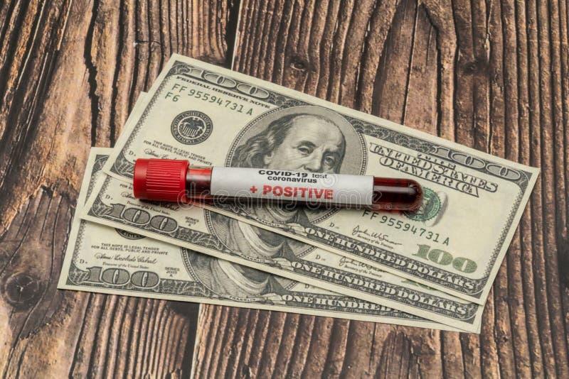 COVID 19 Coronavirus, infekterat blodprov i provröret, på US dollar, läkemedelsföretag arkivfoton