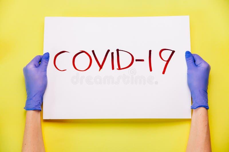 COVID-19 Coronavirus kreativt koncept Handskar i handskar som håller affisch vith `COVID-19` ord arkivbilder