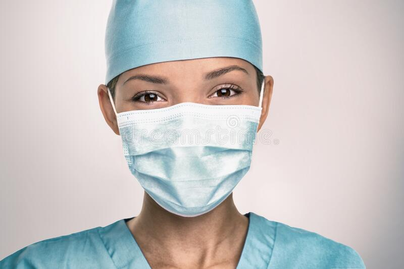 COVID-19 Coronavirus pandemic happy Asian doctor positive with hope wearing surgical mask and blue protective scrubs at. Hospital. Inspiring confidence in the royalty free stock photo