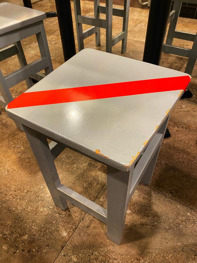Covid 19 Coronavirus Social Distancing Stool Chair with a Red Tape over the Top. Customers aren't allow to sit on any stool chairs that has got a red tape royalty free stock image
