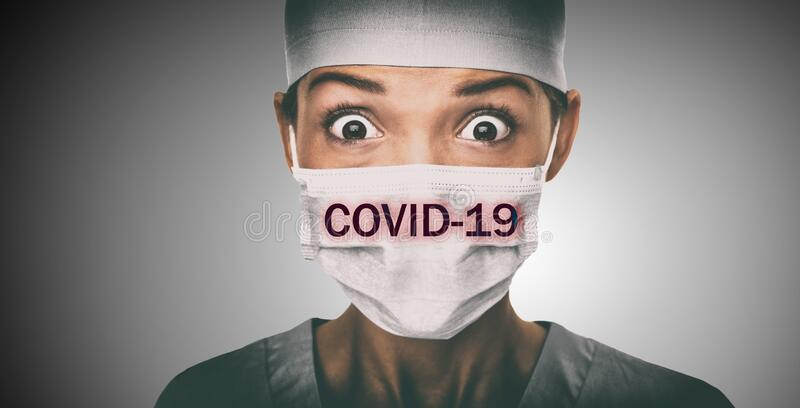 Covid-19 coronavirus text written over doctor surgical face mask Asian woman hospital worked scared shocked by Corona. Virus pandemic worried. Title on stock image
