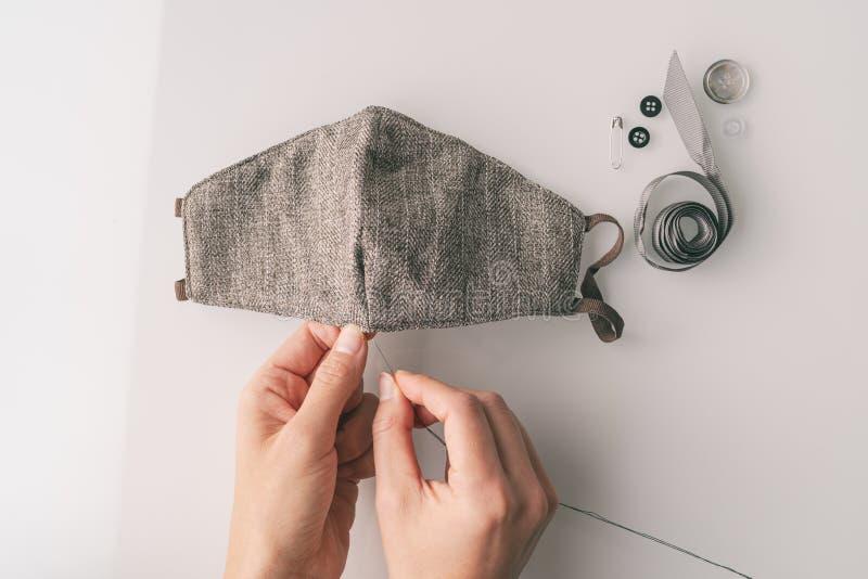 COVID-19 die DIY-gezichtsmaskers maakt bij het masker van het huisnaaiweefsel om medische zorgverleners met een PPE-tekort te hel royalty-vrije stock afbeeldingen