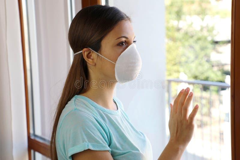COVID-19 Die Isolierung von Frauen im häuslichen Bereich wird automatisch isoliert und trägt Gesichtsmaske, die den Schutz vor de lizenzfreie stockbilder
