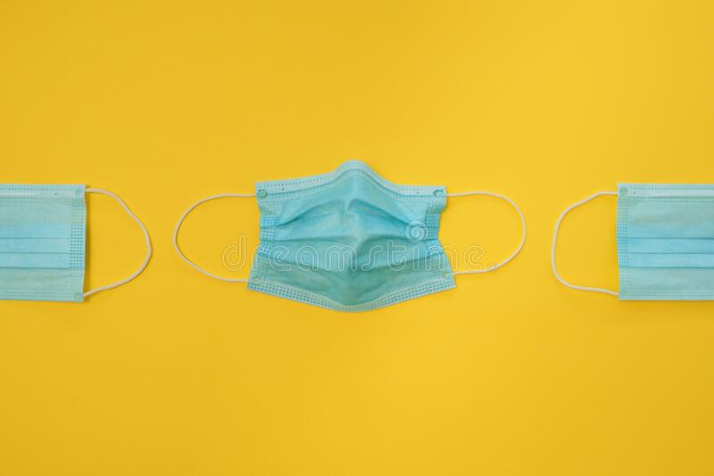 COVID-19 disposable surgical face masks on yellow background stock image