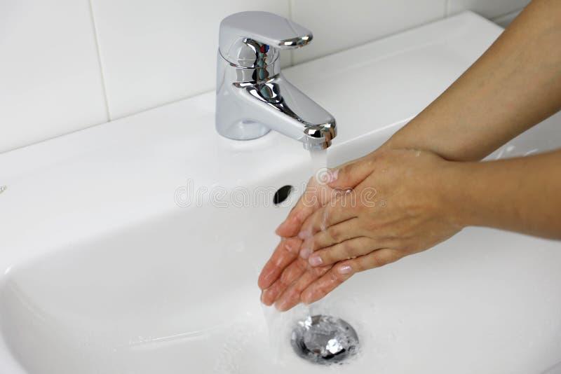 COVID-19 Lavar as mãos na pia do banheiro em casa contra o Novel coronavirus 2019-nCoV Conceito de higiene e cuidados de saúde fotos de stock royalty free