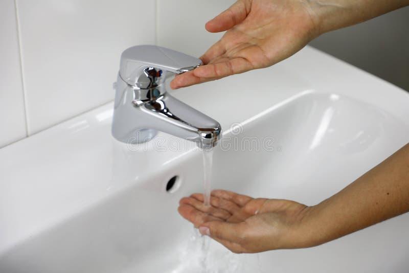COVID-19 Lavare le mani nel lavandino del bagno a casa contro Novel coronavirus 2019-nCoV Le mani della donna controllano la temp fotografie stock libere da diritti