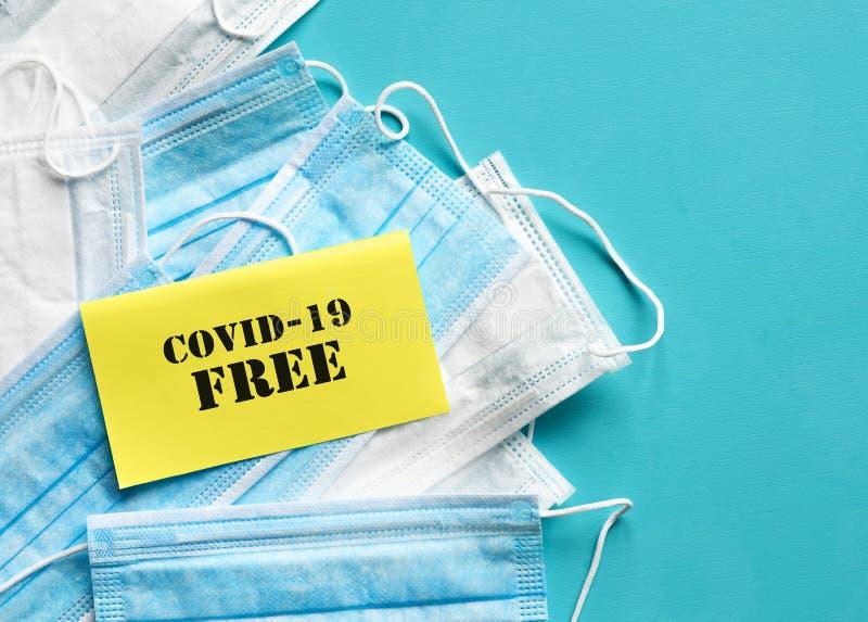 COVID-19 Letteratura GRATUITA su carta gialla su sfondo blu Maschere di respirazione per la protezione contro immagini stock