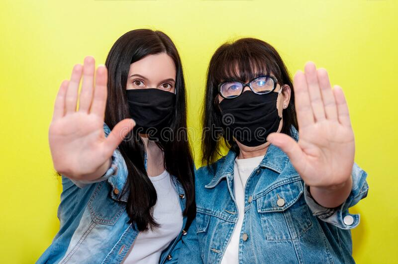 COVID-19. Mother and Daughter in Protective Medical Face Mask Show Palm Hand Sign Stop. Anti-Coronavirus Concept. COVID-19. Mother and Daughter in Protective stock photography