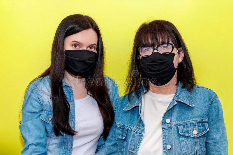 COVID-19. Mother and Daughter in Protective Medical Face Mask on Yellow Background. Anti-Coronavirus Concept.  stock photo
