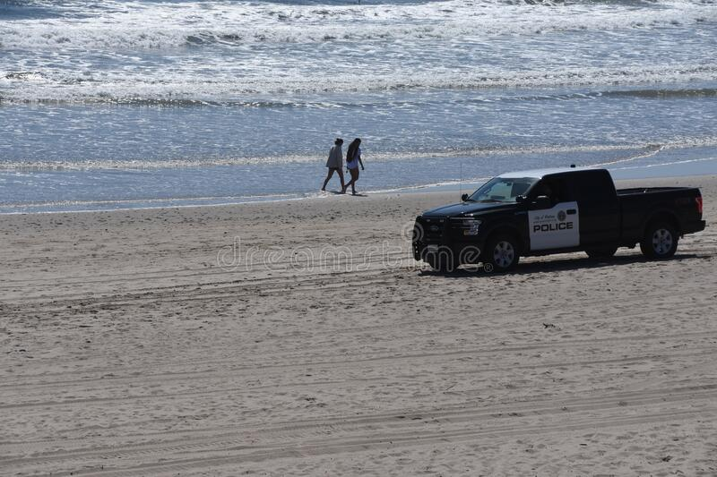 Covid-19 police patrol truck on the beach royalty free stock photo