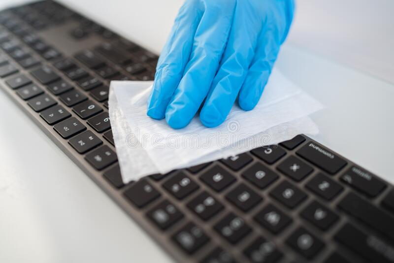 Covid-19 sanitizing office space wiping corona virus cleaning and disinfection of your workspace. Disinfecting wipes to. Wipe surface of desk, keyboard, mouse stock image