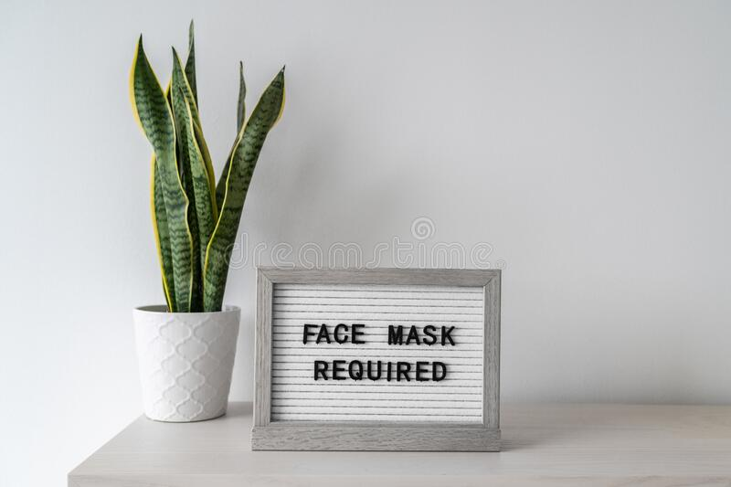 COVID-19 sign requiring customers to wear a mask at business store. Coronavirus preventive measure notice with text face royalty free stock photos