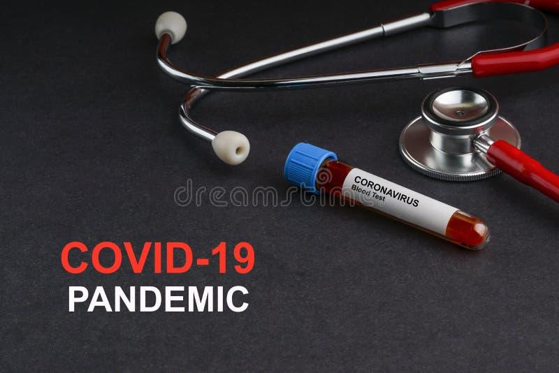 COVID-19 Texto PANDEMIC com estetoscópio e tubo de vácuo de amostra sanguínea imagem de stock