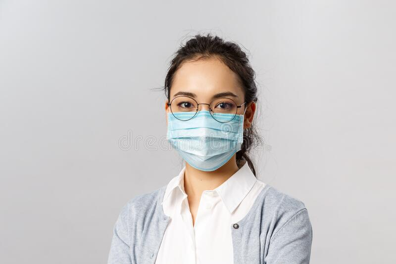 Covid19, virus, health and medicine concept. Portrait of young asian woman wearing medical face mask to prevent getting. Infected by coronaviruts, staying safe stock image