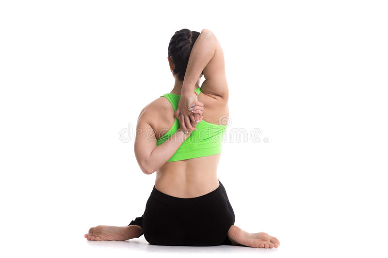 Cow face yoga asana. Sporty girl doing yoga training, sitting in Gomukhasana, Cow face pose, asana for stretching triceps, shoulders, hips and thighs, arms royalty free stock photos