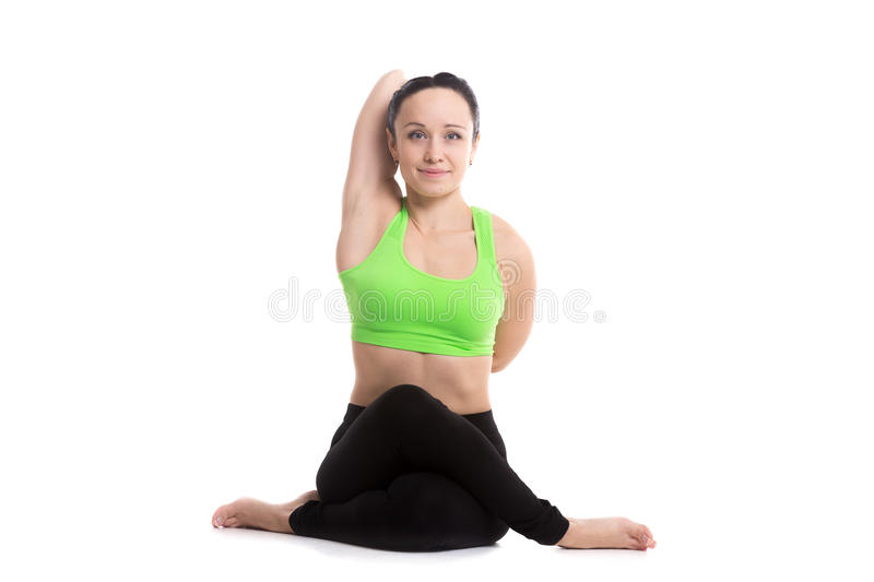 Cow face yoga pose. Smiling sporty girl doing yoga practice, sitting in Gomukhasana, Cow face pose, asana for stretching triceps, shoulders, hips and thighs stock images