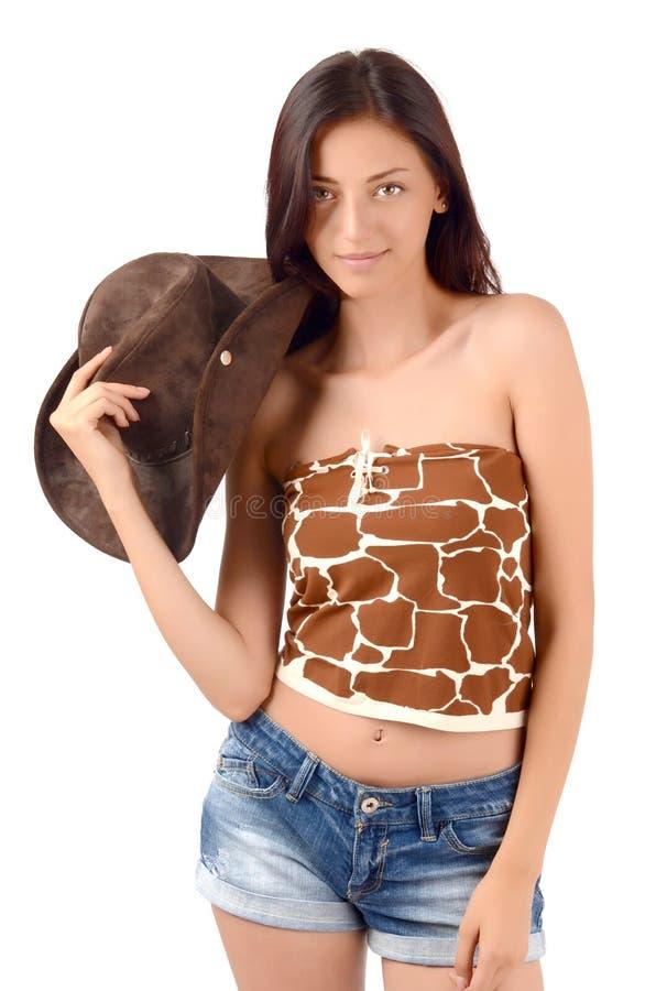 Cow-girl américaine sexy avec des shorts de jeans, un dessus et un chapeau de cowboy. photos stock