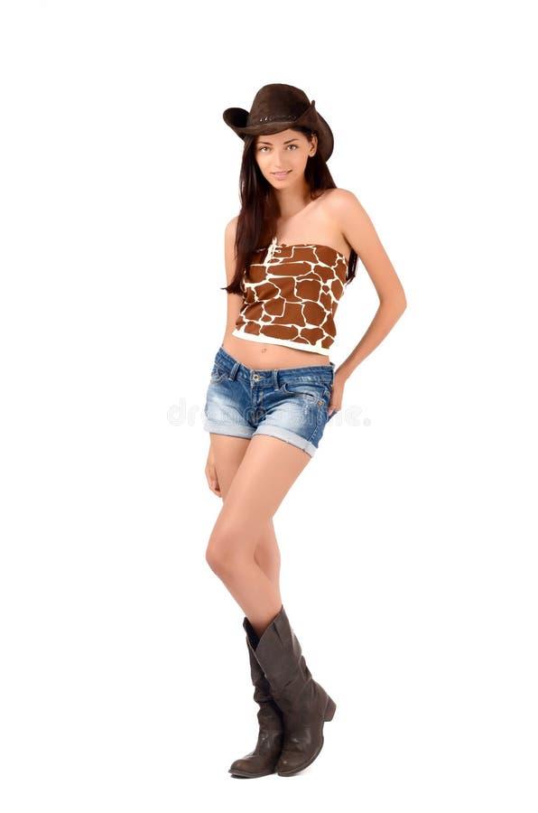 Cow-girl américaine sexy avec des shorts et des bottes et un chapeau de cowboy. images libres de droits