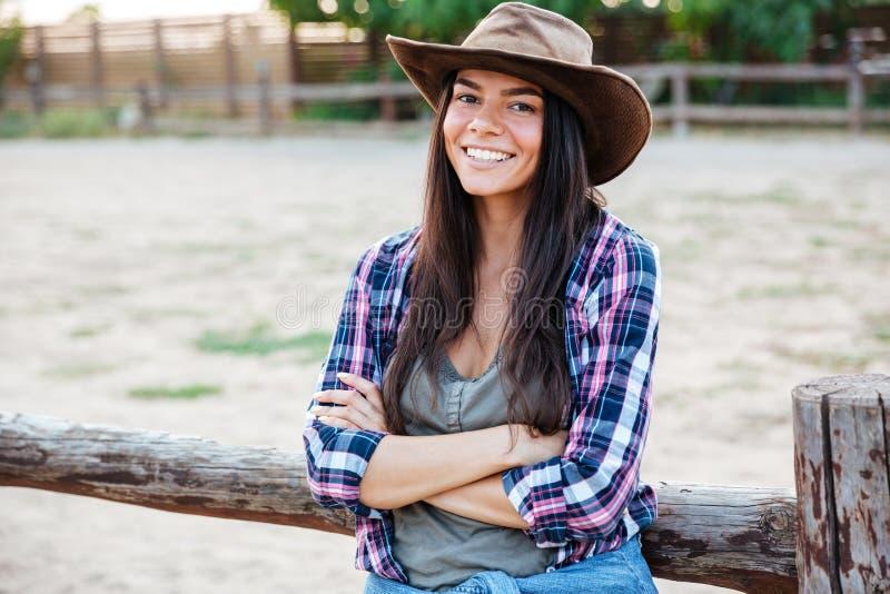 Cow-girl attirante gaie de jeune femme se tenant avec des bras croisés photos stock