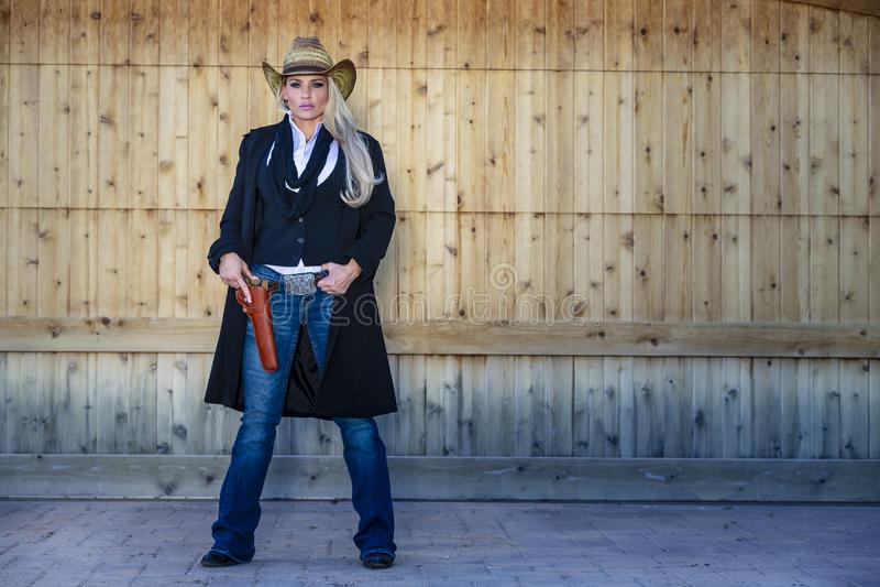 Cow-girl blonde avec des armes dans le sud-ouest américain photographie stock libre de droits