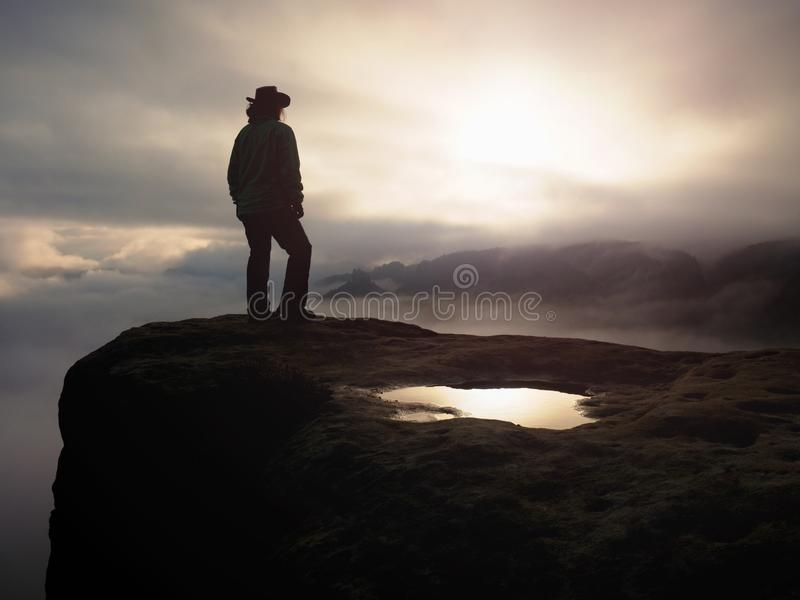 Cow girl in cowboy hat on mountain peak look into heavy mist royalty free stock images