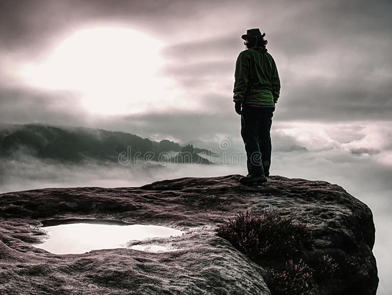Cow girl in cowboy hat on mountain peak look into heavy mist royalty free stock photos