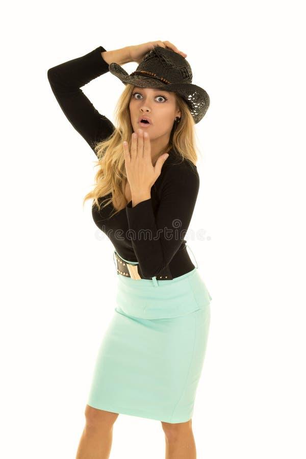 Cow-girl dans la main verte de jupe sur le chapeau choqué photo libre de droits