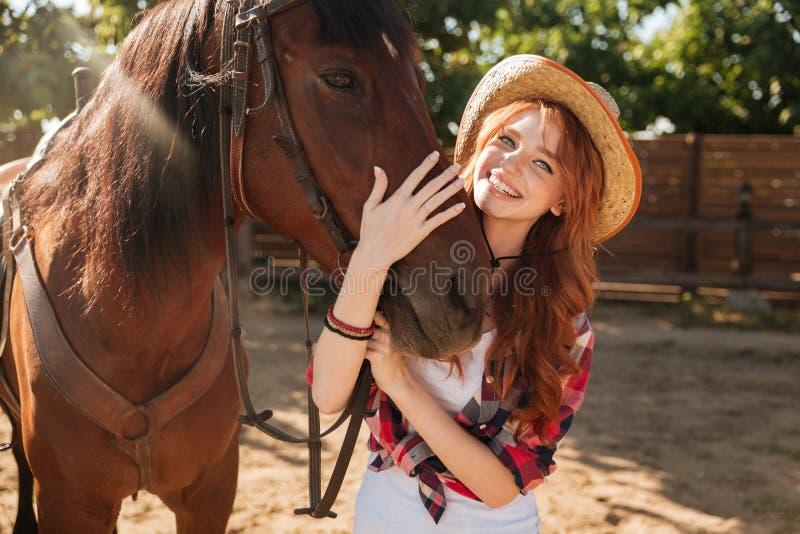Cow-girl heureuse de femme dans le chapeau tenant et étreignant son cheval photo stock