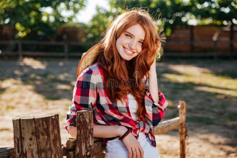 Cow-girl heureuse de femme se tenant et souriant à la ferme photographie stock libre de droits