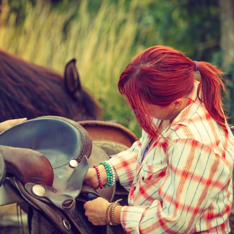 Cow-girl obtenant le cheval prêt pour le tour sur la campagne image stock