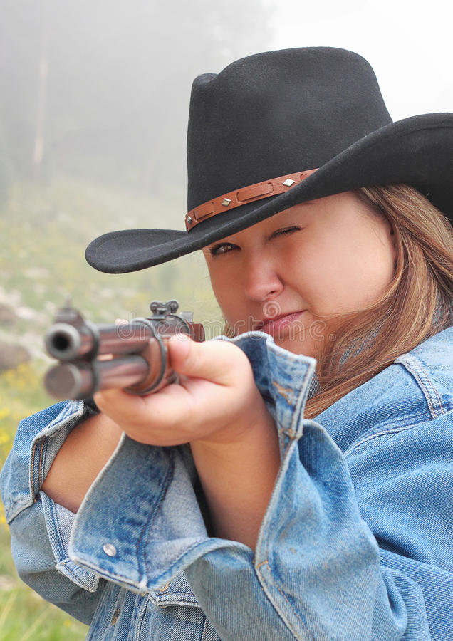Cow-girl orientant le fusil image stock