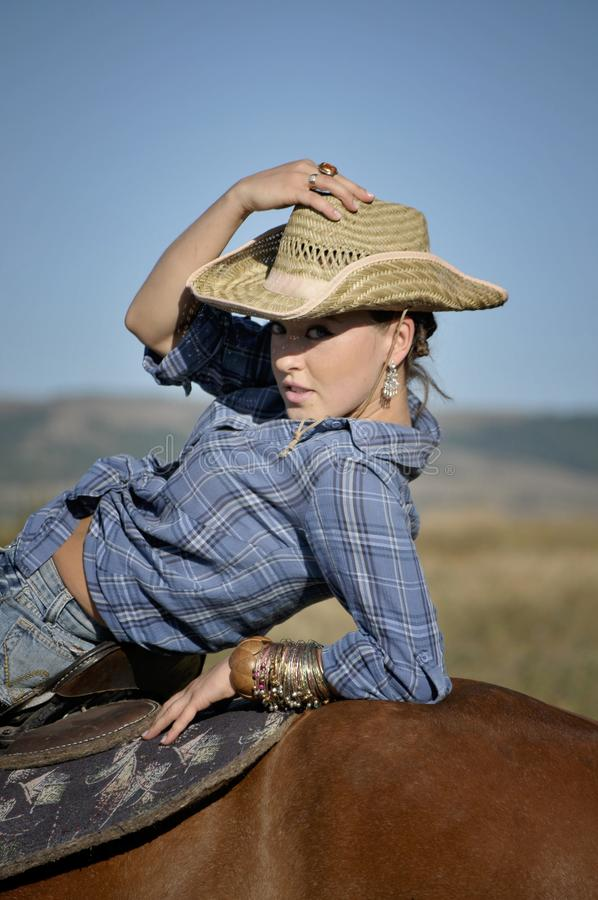 Cow-girl séduisante dans un chapeau de paille sur le cheval photos stock