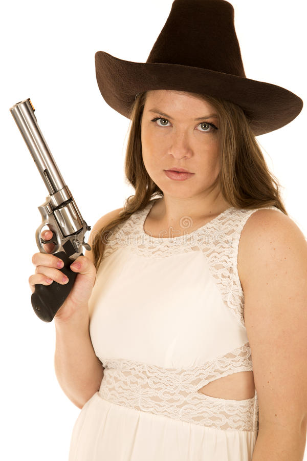 Cow-girl sérieuse tenant un pistolet portant une robe blanche photo stock