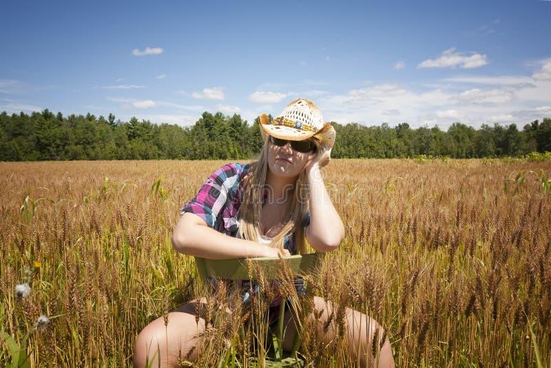 Cow-girl s'asseyant dans le domaine de blé photos stock