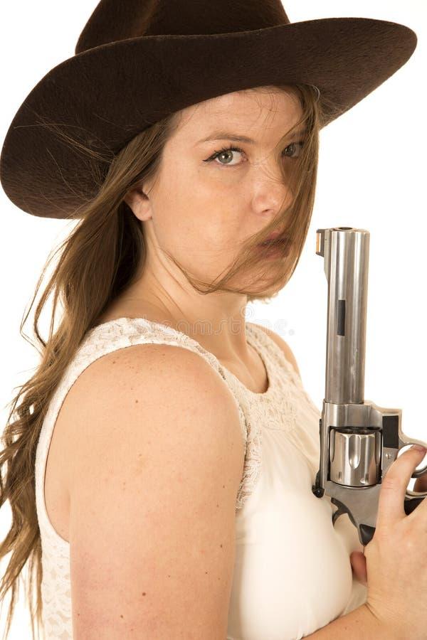 Cow-girl tenant un grand revolver avec une expression sérieuse photographie stock libre de droits