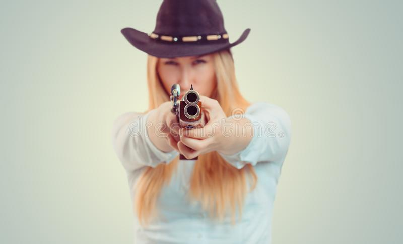 Cow-girl visant la caméra avec l'arme à feu image libre de droits